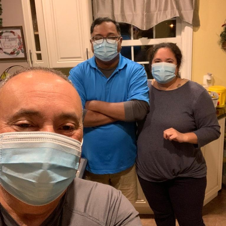 A husband and wife masked, and older gentleman masked.