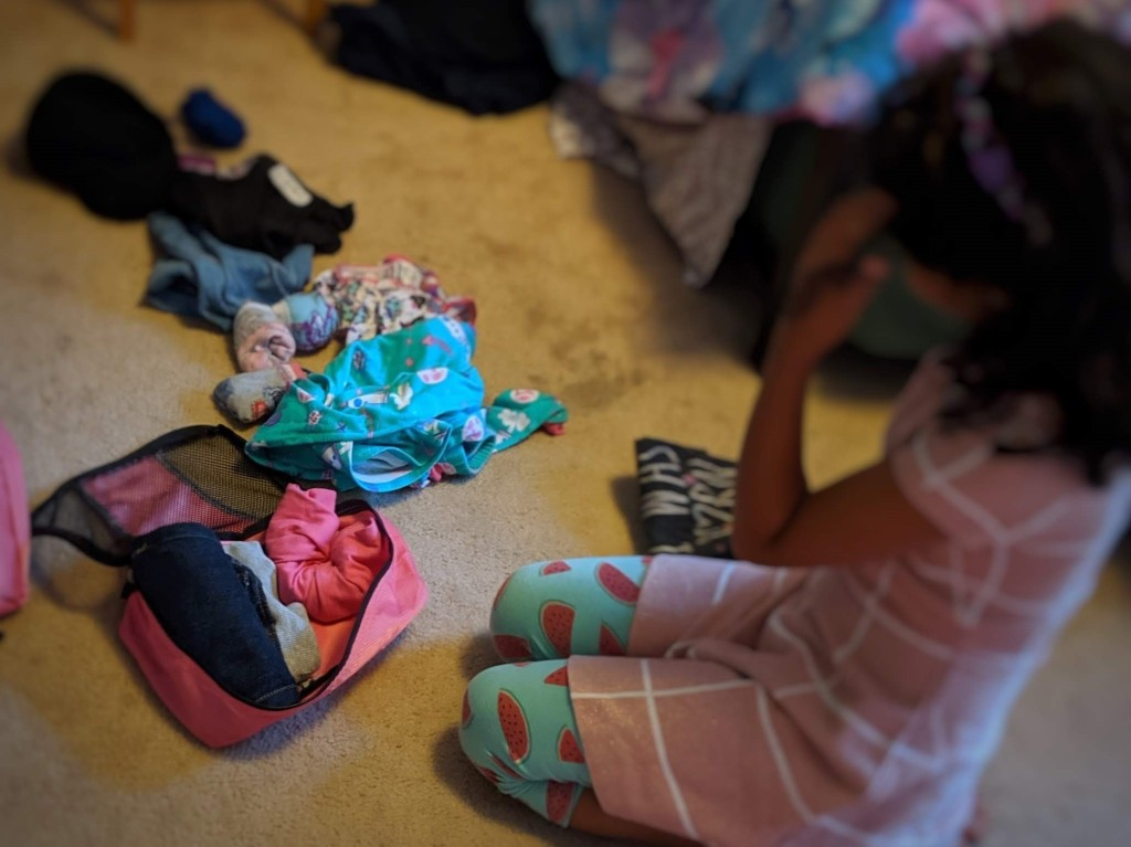 Young girl packing clothes in a packing cube