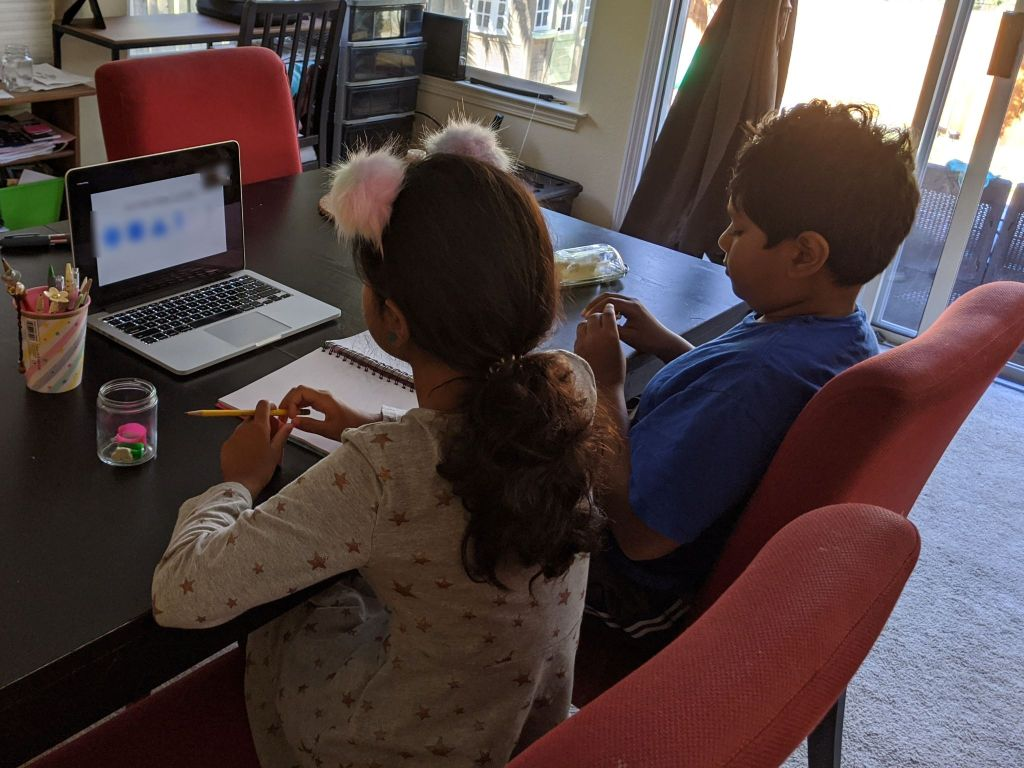 Two kids at a table working on a computer