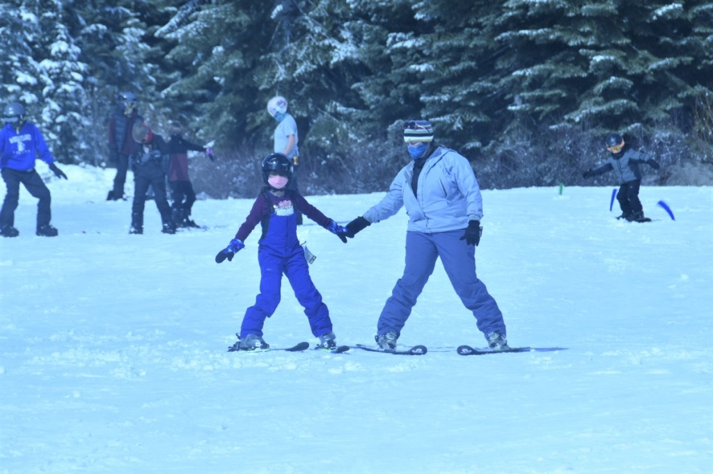 A young girl in a ski bib holding the hands of an adult skier helping her down the hill.