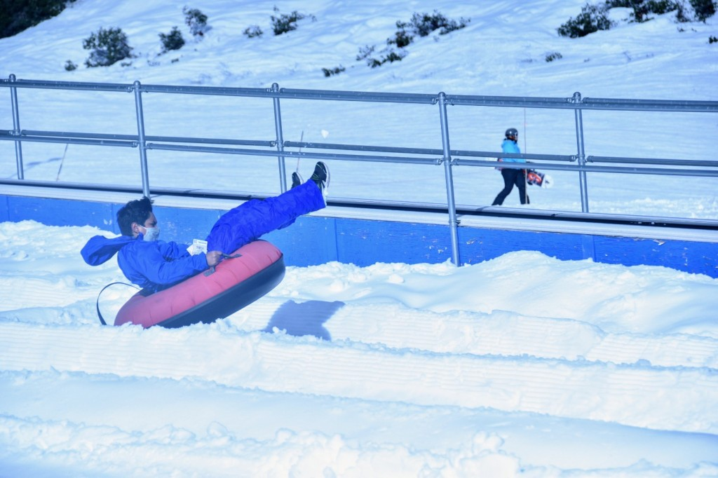 A young man in an inner tube catching some air as they hit a bump during a downhill snow run.